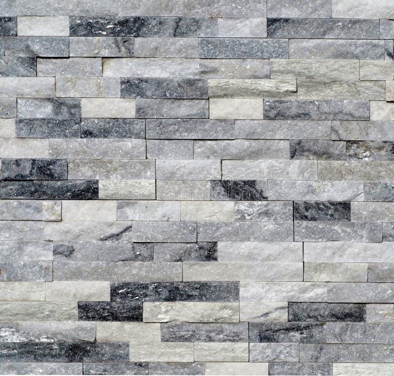 Cladding för stenvägg som göras av vita och gråa kvartsittegelstenar arkivfoto