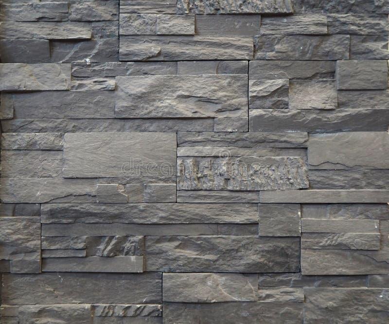 Cladding för stenväggen som göras av gråa kvarter och tegelstenar av naturligt, vaggar royaltyfri fotografi