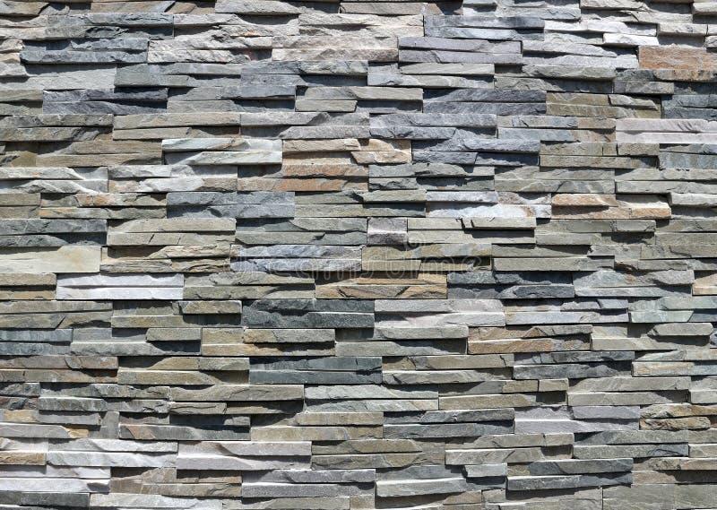 Cladding för stenväggen som göras av ojämnt naturligt, vaggar remsor av olika färger royaltyfri fotografi