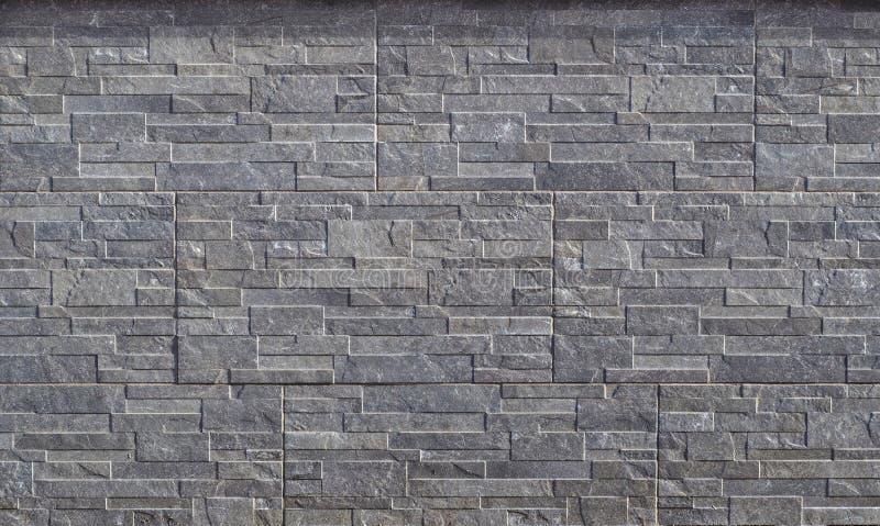 Cladding för stenväggen som göras av präglade horisontalgråa band av, vaggar staplat i paneler royaltyfri bild
