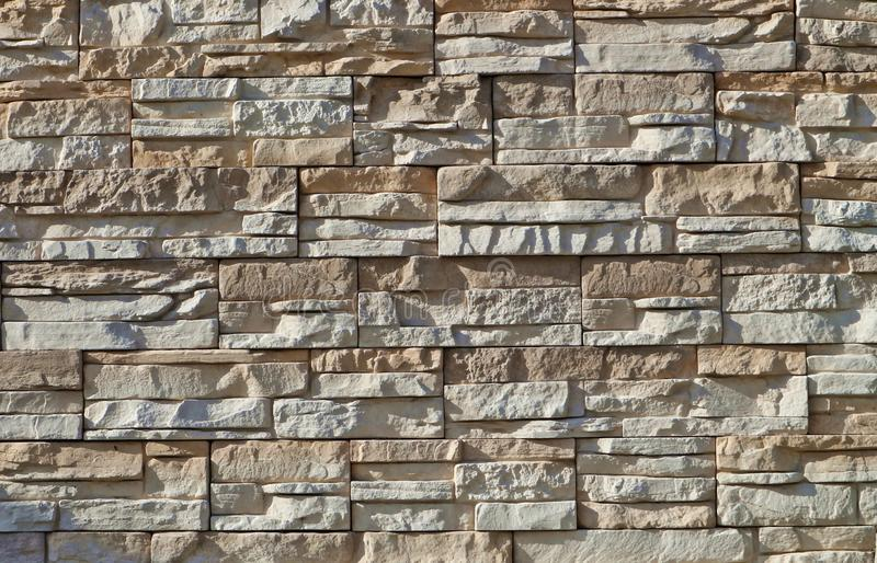 Cladding för stenväggen som göras av staplad ojämnt och horisontal, vaggar remsor Färger är vita och ljusa - brunt arkivbilder