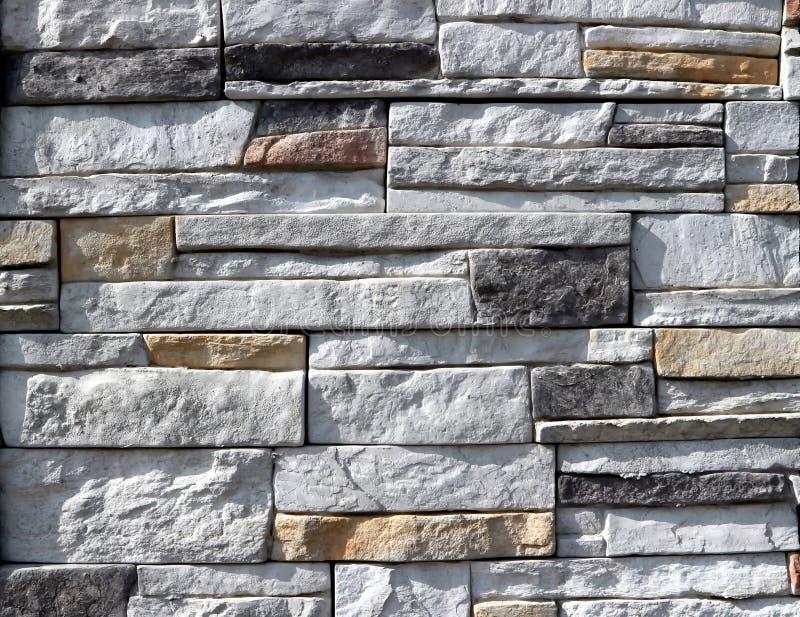 Cladding för stenväggen som göras av staplad vit, vaggar med mellanlägget av brunt- och svartstenar royaltyfria bilder