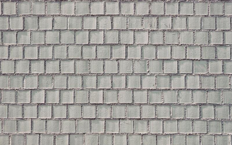 Cladding för yttre vägg som göras av grovt ljus - gråa fyrkantiga cementtegelplattor Bakgrund och textur med kopieringsutrymme royaltyfri fotografi