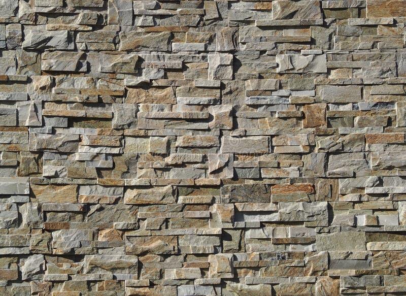 Cladding för yttre vägg som göras av naturliga stenar med ojämna former Färger är skuggor av grått och brunt royaltyfria foton