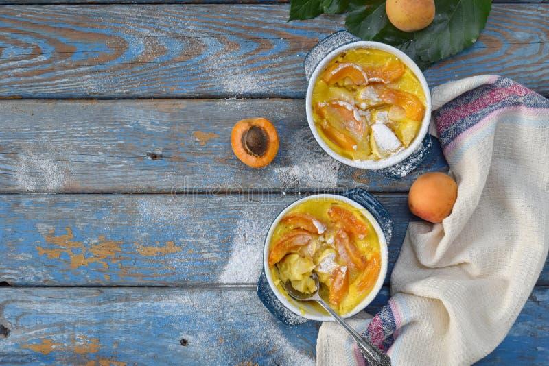 Clafouti с абрикосами внутри rameken на голубой деревянной предпосылке Clafoutis плодов Сладкий сотейник Традиционный французский стоковые фотографии rf