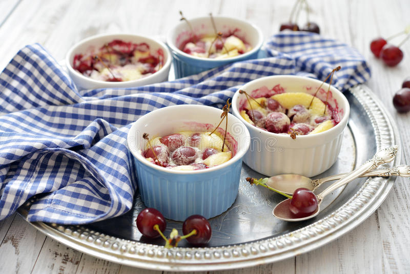 Clafoutis with cherries. In red ramekin on wooden background stock photo