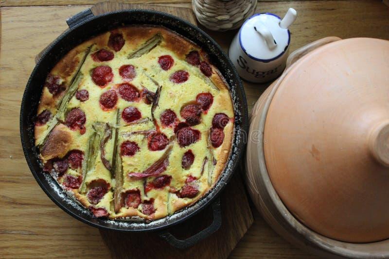 Clafoutis de fraise et de rhubarbe avec la poubelle de casserole et de sucre d'argile photos libres de droits