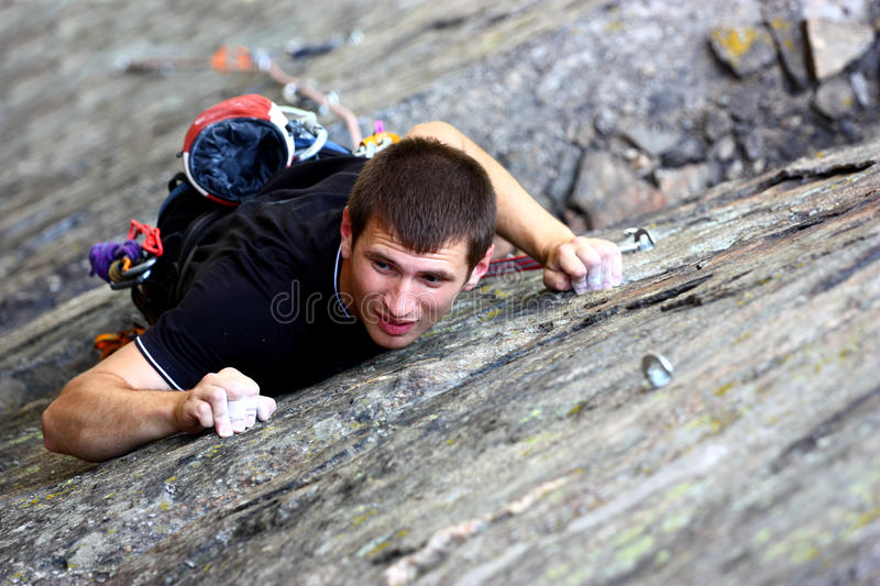 Claiming a stone wall. Young male climber claiming a stone wall outdoor royalty free stock image
