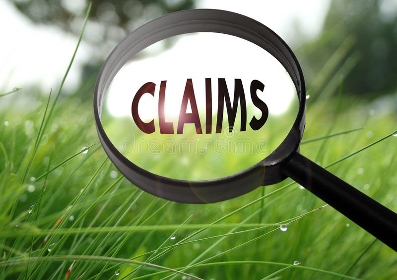 Claims. Magnifying glass with the word claims on grass background. Selective focus royalty free stock photos