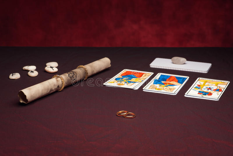 Clairvoyance equipment with weddings rings. On dark desk stock photography