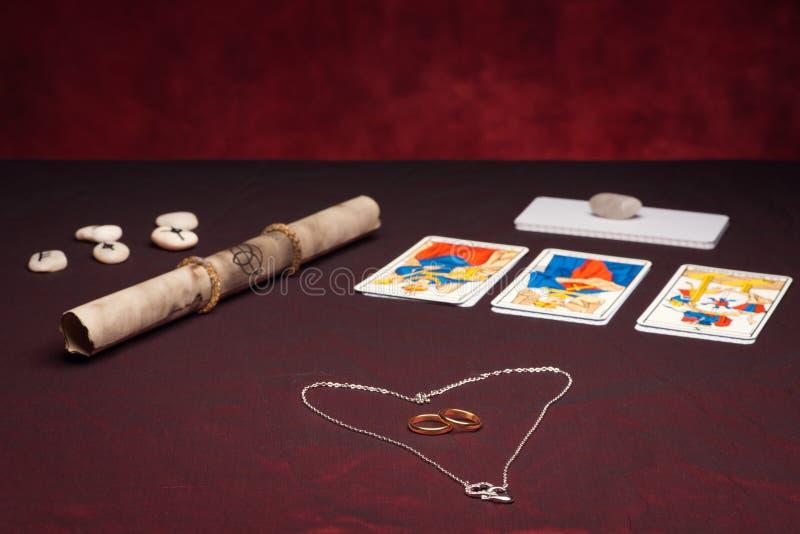 Clairvoyance equipment with weddings rings. On dark desk stock photos