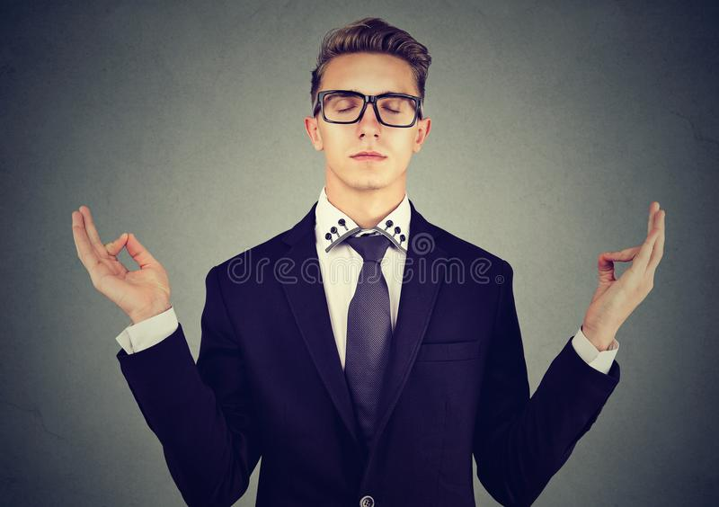 Young business man meditating relaxing with eyes closed stock photo