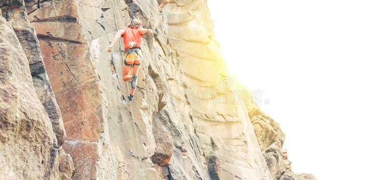 clambing岩石墙壁在日落-登山人的运动人执行在做一个杂技跃迁的峡谷山 免版税库存照片