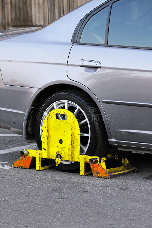 Clamp. Restricted park vehicle with yellow wheel clamp royalty free stock photo