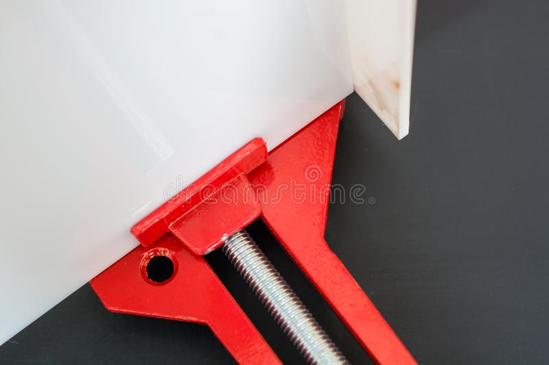 Clamp holding the slat. Part of Red clamp on black background. Clamp holding the slat royalty free stock photo