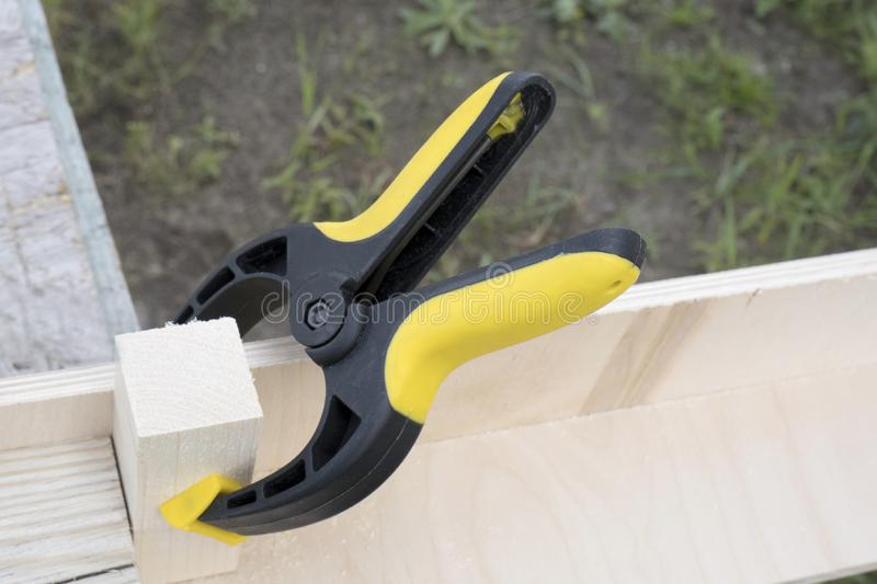 Clamp with plywood and a piece of pine wood. Construction, woodwork, carpentry concept royalty free stock photography
