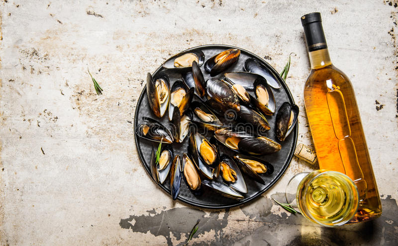 Clams on a tray with wine. On rustic background. royalty free stock photos