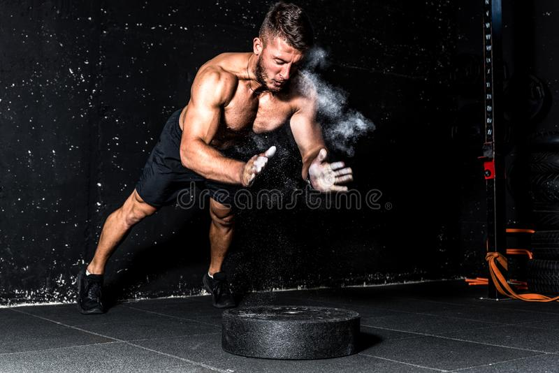 Young muscular man with big sweaty muscles doing push ups workout training with clap his hand above the barbell weight plate on th. Clap push ups, Young muscular royalty free stock image