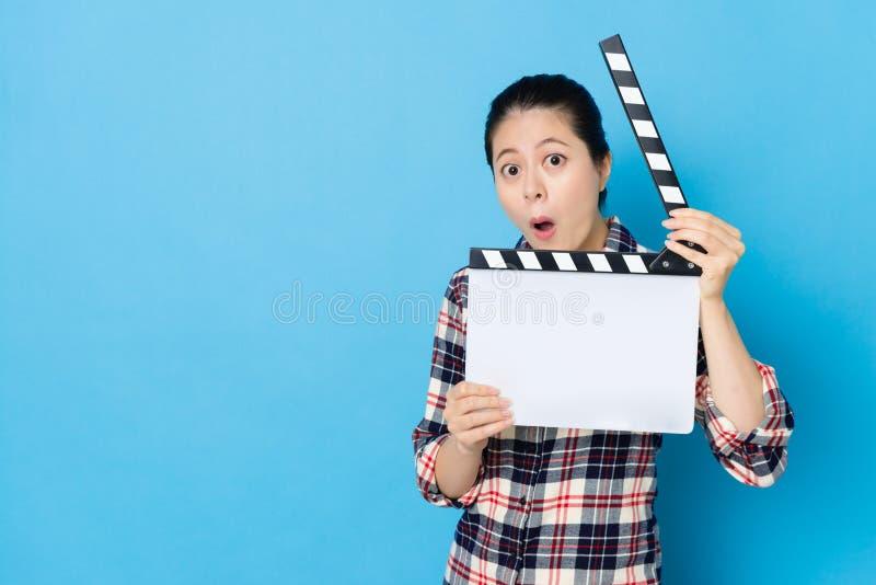 Clapboard παιχνιδιού γυναικών που εξετάζει τη κάμερα στοκ εικόνες