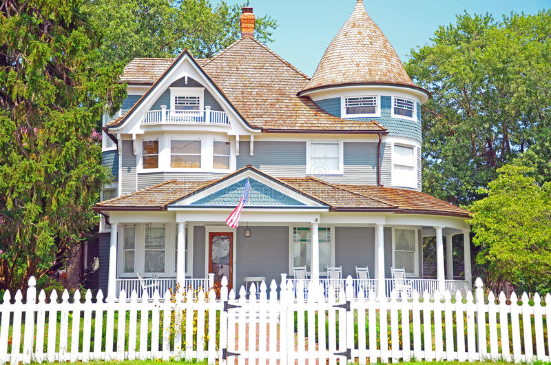 Clapboard House. A blue clapboard house behind a white picket fence symbolizes the American Dream stock photo