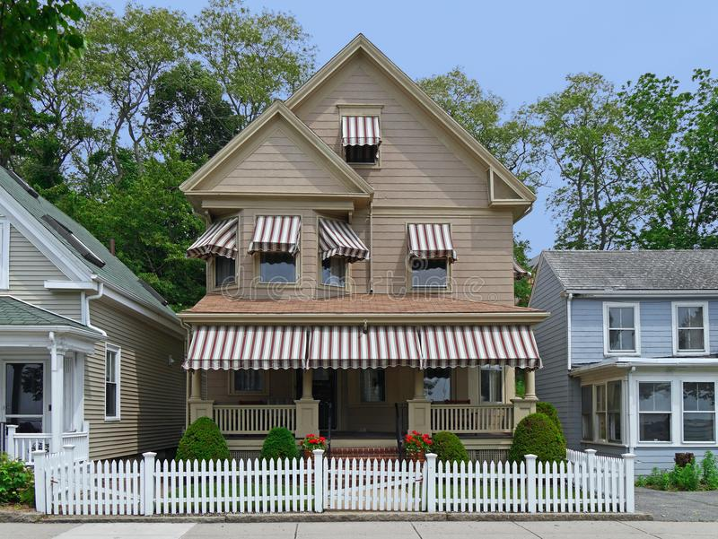 Clapboard house with large porch. And white picket fence royalty free stock image
