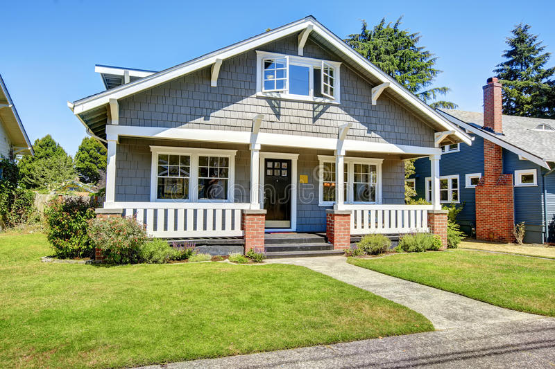 Clapboard siding house exterior. Large entance porch with brick. Trim and white railings stock photography