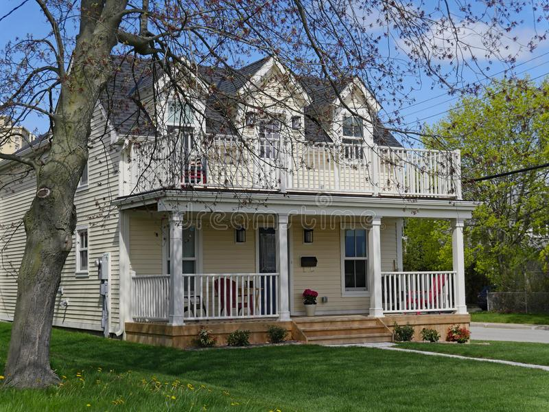 Clapboard siding house with double-decker porch. Clapboard siding house with gable dormer windows and double decker porch royalty free stock photography