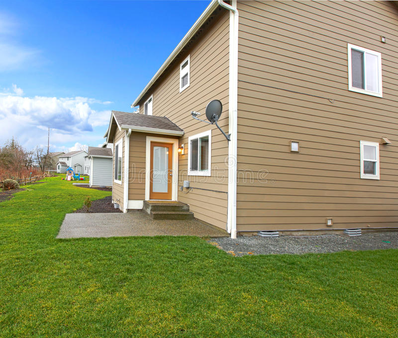 Clapboard siding house with a green lawn. Two story beige clapboard siding house with and orage frame door and concrete small poch. View from the green lawn stock photos