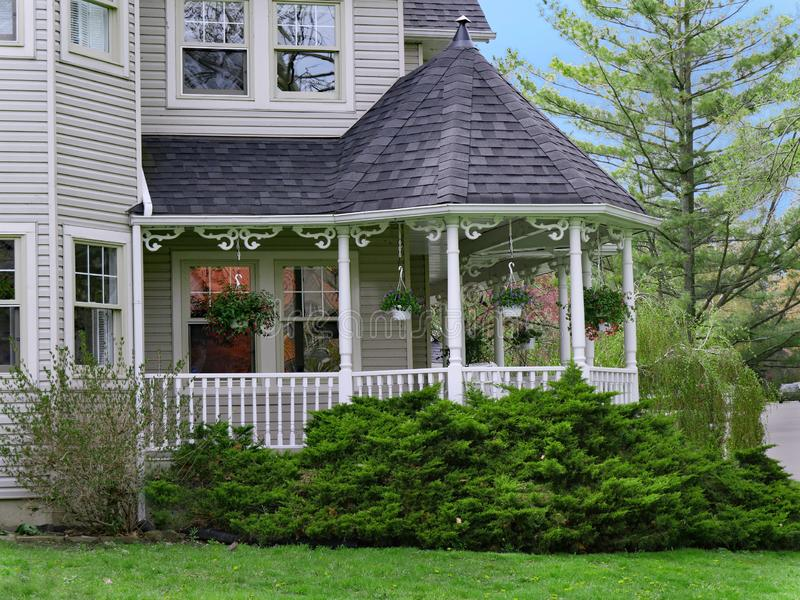 Clapboard siding house with wrap-around porch. With cone shaped roof stock image