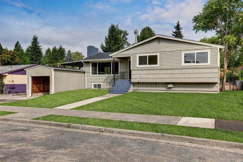 Clapboard siding one story house exterior. Clapboard siding one story house exterior on a sunny day. Grass filled front yard. Garage with opened door. Northwest stock photos
