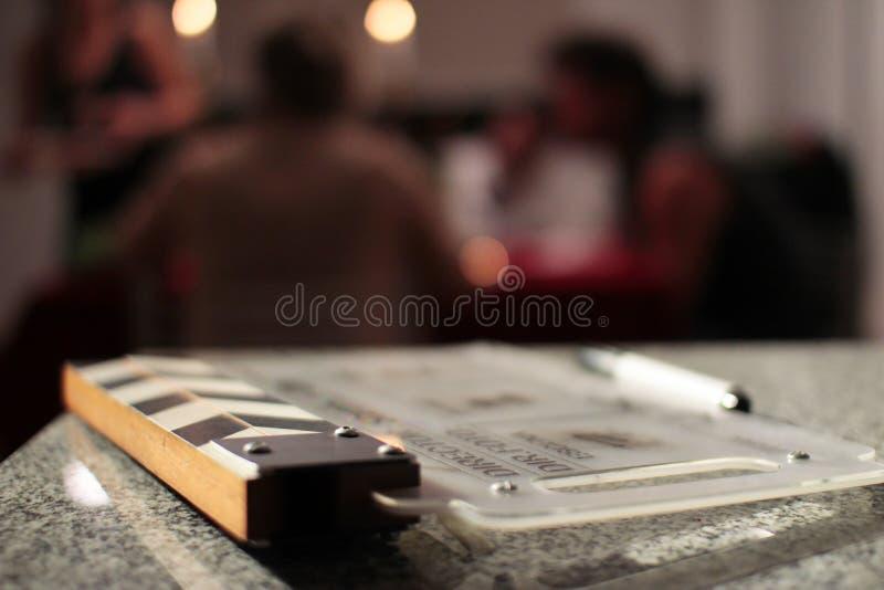 Clapperboad de film avec les personnes brouillées sur le fond images stock