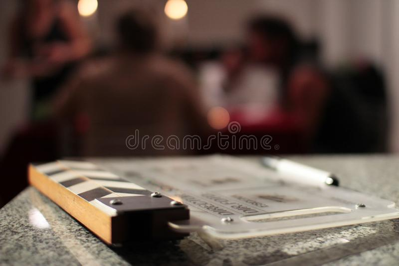 Clapperboad de la película con la gente borrosa en el fondo imagenes de archivo