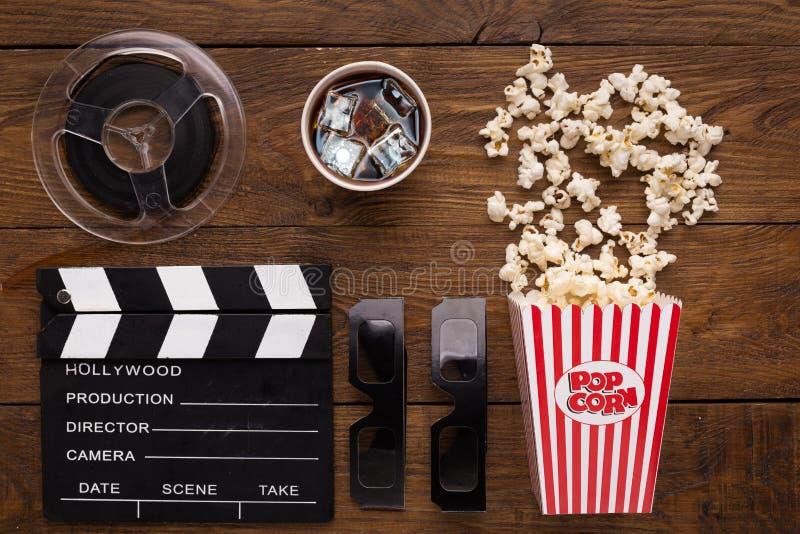 Clapperboard、影片轴和玉米花在木背景,顶视图 免版税库存照片