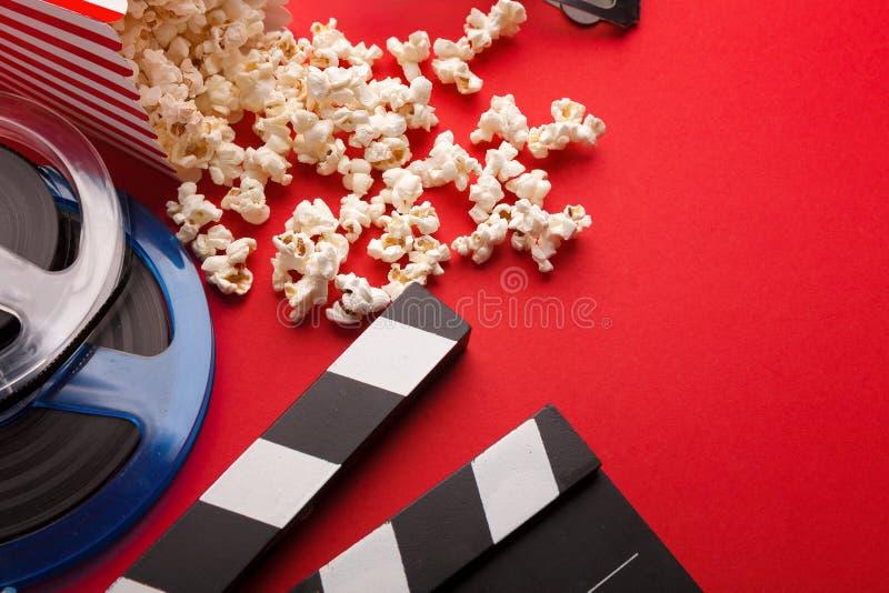 Clapperboard、影片轴和玉米花在红色背景 免版税图库摄影