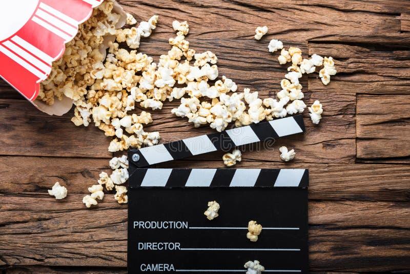 Clapperboard和玉米花在代表电影放映时间的木头 库存图片