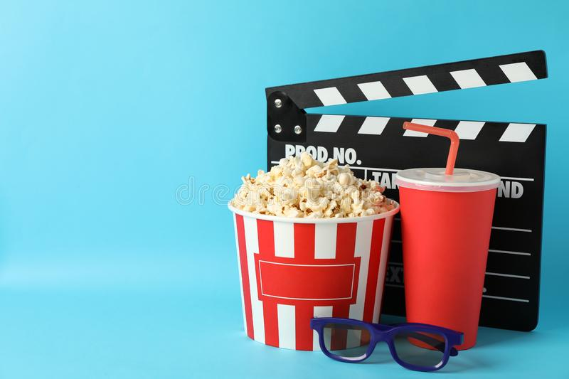 Clapperboard, bucket with popcorn, drink and 3d glasses. On blue background royalty free stock image