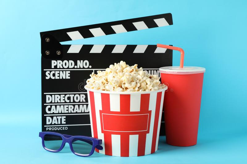 Clapperboard, bucket with popcorn, drink and 3d glasses. On blue background stock images