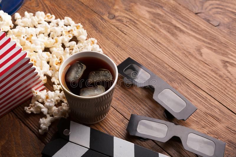 Clapperboard, film reel and popcorn on wooden background stock image