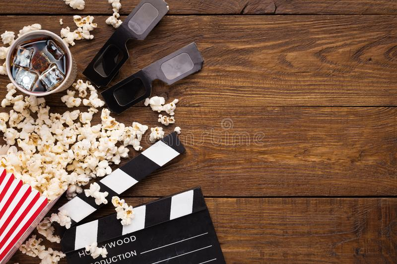 Clapperboard, film reel and popcorn on wooden background, top view royalty free stock image
