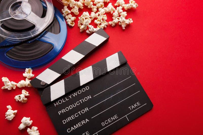 Clapperboard, filmrulle och popcorn på röd bakgrund arkivfoton