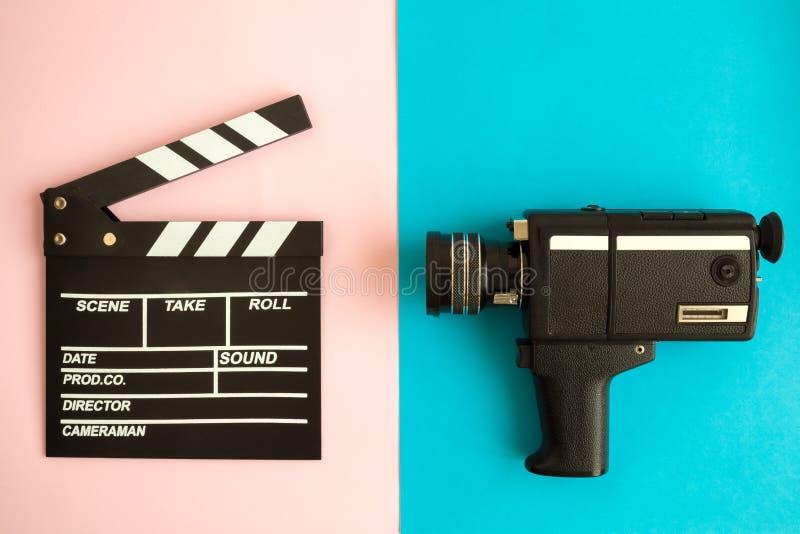 Clapperboard och tappningvideokamera på mångfärgad bakgrund royaltyfria foton