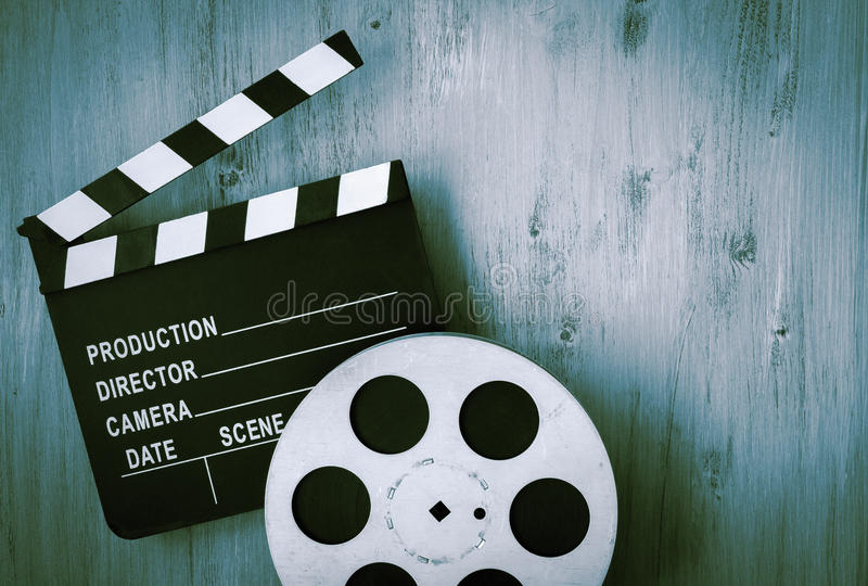 Clapperboards and the reel of film. Lie on a wooden board stock image