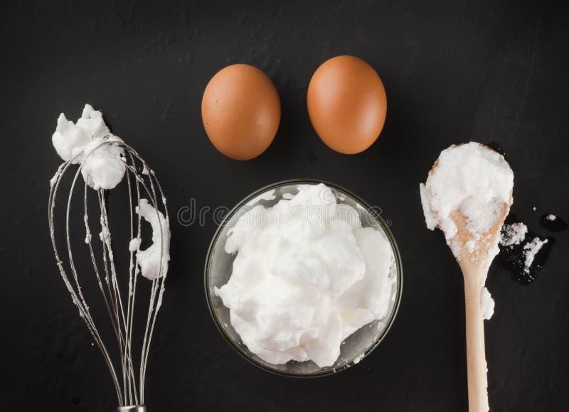 Claras de ovos chicoteadas para o creme em uma bacia de vidro, em um batedor de ovos e em um s de madeira fotografia de stock royalty free