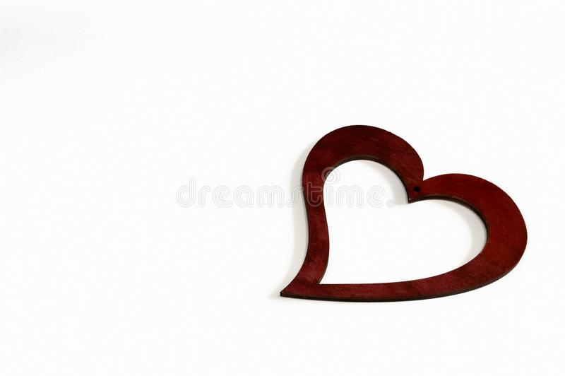 Claret painted wood heart with white background with love. Claret heart for Valentine`s Day, this made of wood and colored in red paint royalty free stock photos