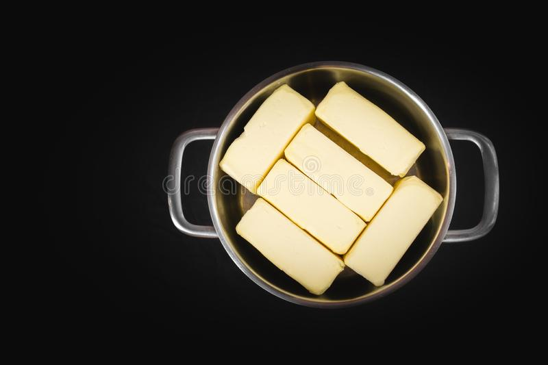 Clarification of butter, butter cubes in a steel pot on a black isolated background, top view. Cooking theme royalty free stock photography