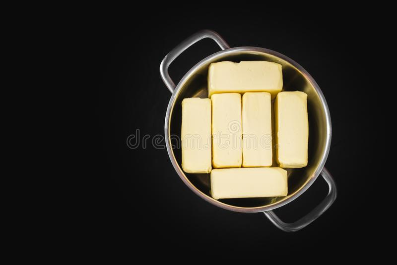 Clarification of butter, butter cubes in a steel pot on a black isolated background, top view. Cooking theme royalty free stock image