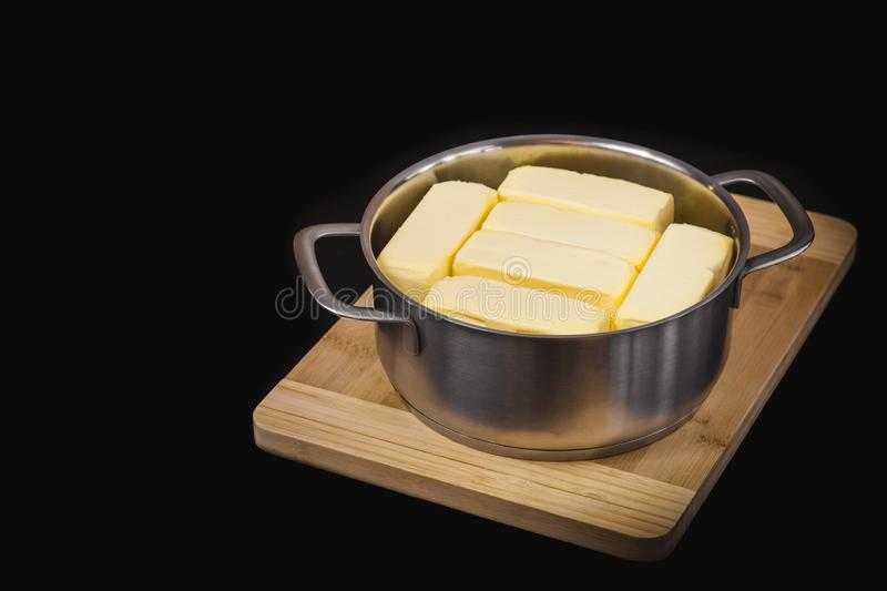 Clarification of butter, butter cubes in a steel pot on a chopping board and black isolated background. Cooking theme stock image