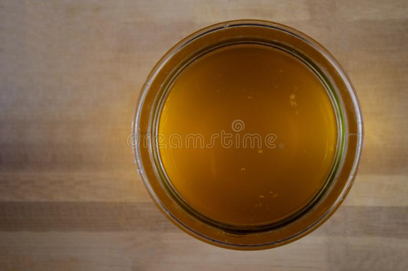 Clarification of butter. Jar full of clarified butter on a wooden background.Top view. Cooking theme royalty free stock photography