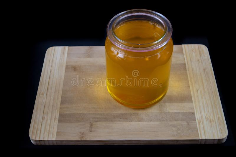 Clarification of butter. Jar full of clarified butter on a wooden chopping board on a black isolated background. Cooking theme stock photography