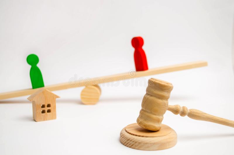 Clarification of ownership of the house. wooden figures of people. rivals in business stand on the scales. competitio, trial, conf. Lict. victory and defeat stock photos